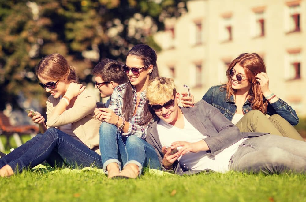 Group of young people in the sunshine looking at their phones