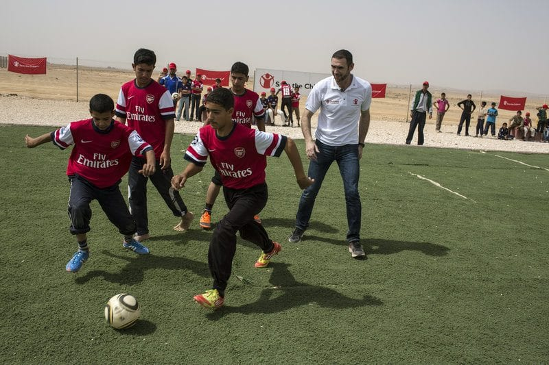Martin Keown plays football on a newly opened pitch in a Jordan refugee camp
