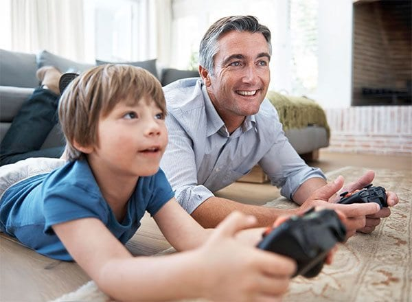 Man and boy with gaming consoles