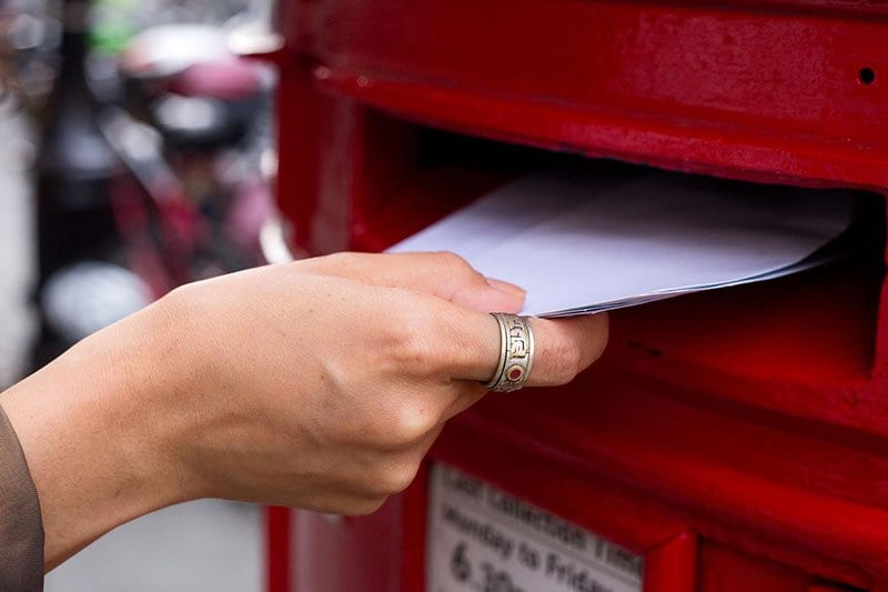 Posting a letter in a red pillarbox