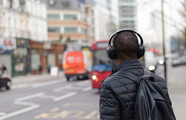 Man wearing headphones about to board a London bus