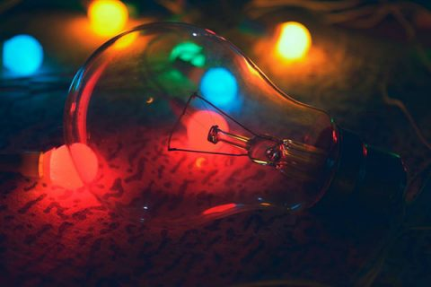 Lightbulb with coloured lights - photo: pexels.com