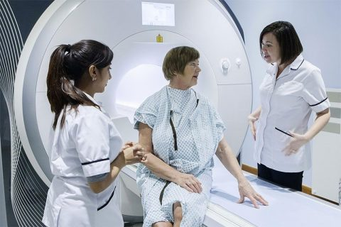 Woman patient and nurses by MRI scanner