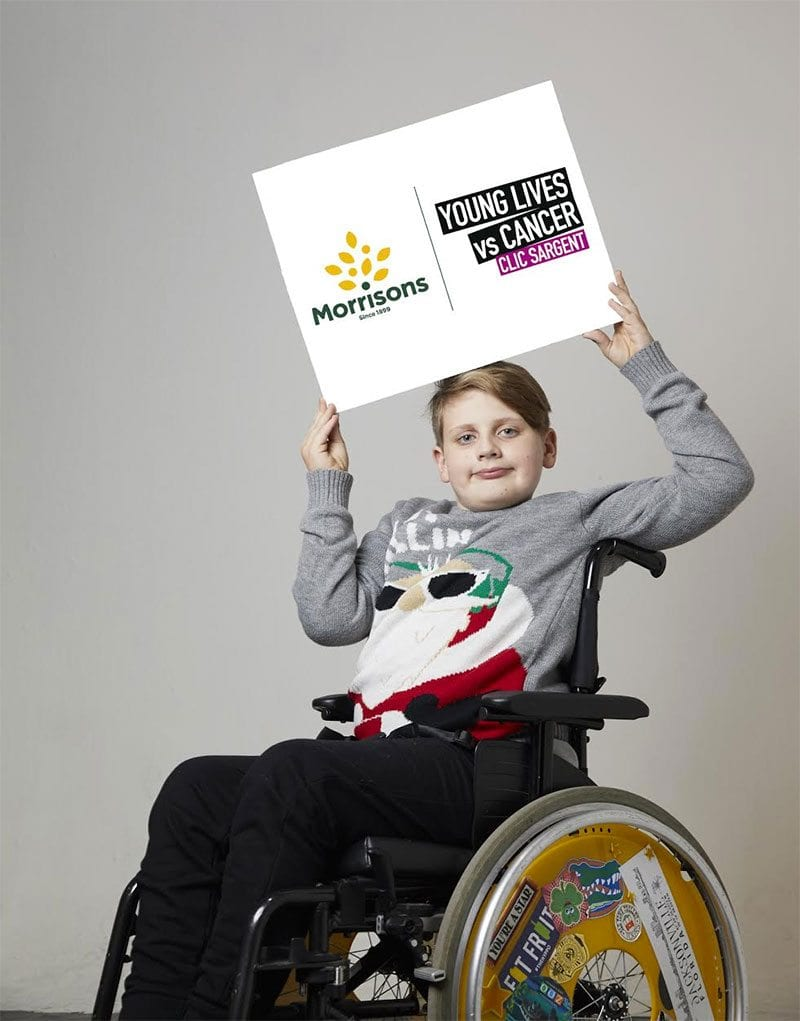 Noah Bailey-Moloney in wheelchair holding Morrisons / CLIC Sargent partnership board