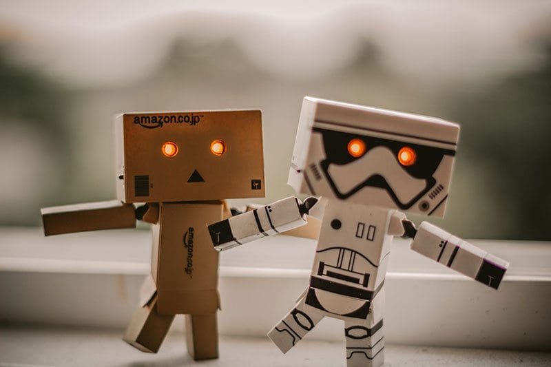Two mini cardboard robots with bright red eyes