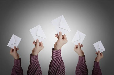 Hands holding up white envelopes