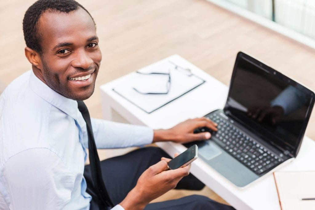 Male black worker using laptop and phone
