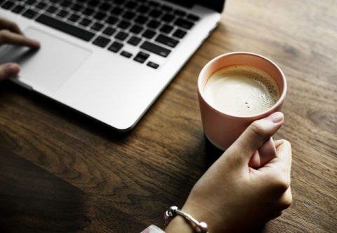 Woman holds coffee on desk beside a laptop