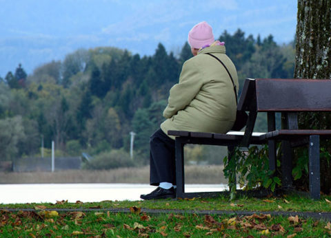 Lonely older woman on park bench