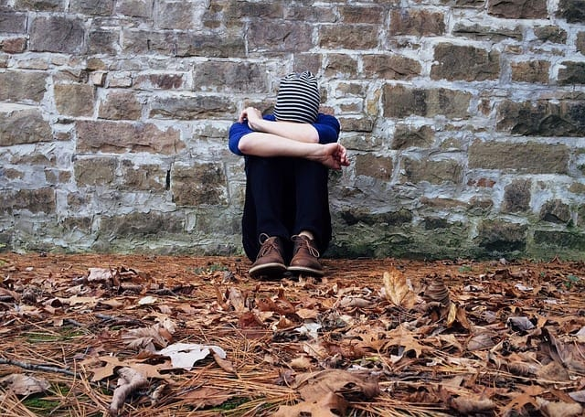 Lonely person sitting against a wall - photo: Pixabay