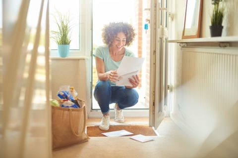 Woman picking up letters from the doormat