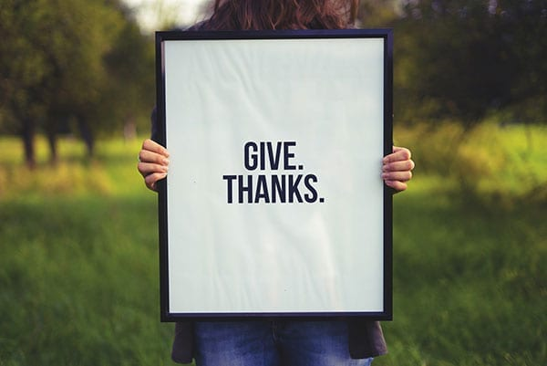 Give.Thanks. Woman holding up sign - photo: Unsplash.com