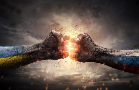Two male fists collide against light, indicating conflict. Image: Shutterstock via Giles Pegram