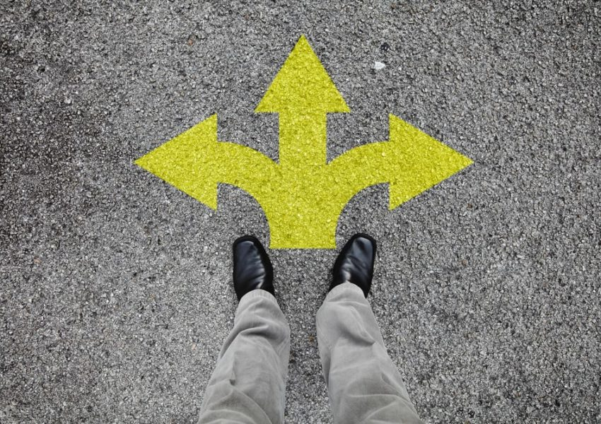 Looking down at two feet with three different arrows painted on ground indicating a choice of direction