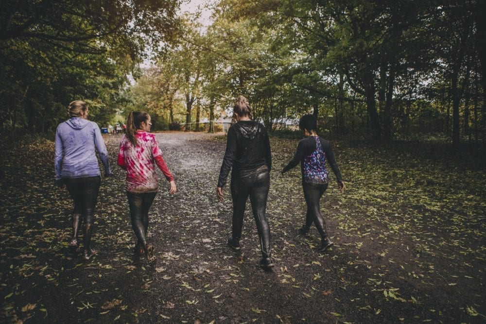 Four women taking part in a charity challenge event in a wood.