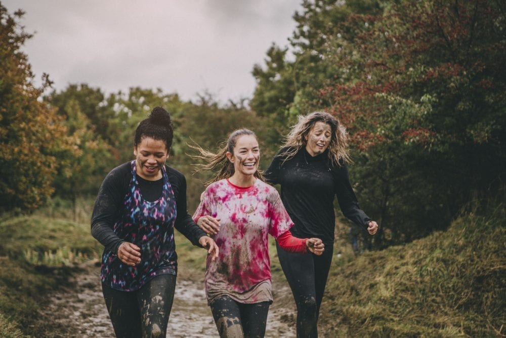 Three women are running through the woods as part of a charity obstacle race.