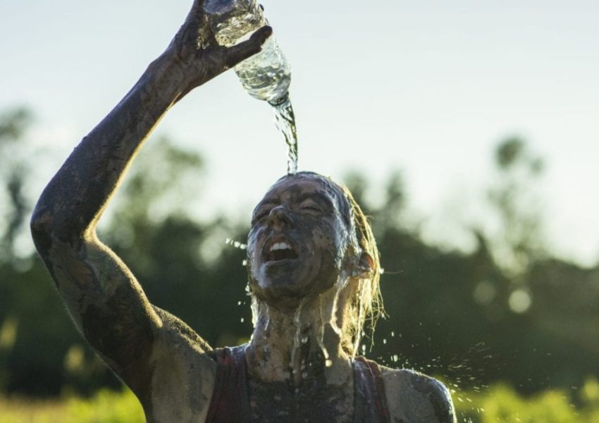 A young woman stands covered in mud while pouring a bottle of water on her face with her mouth open. She is participating in a charity mud run