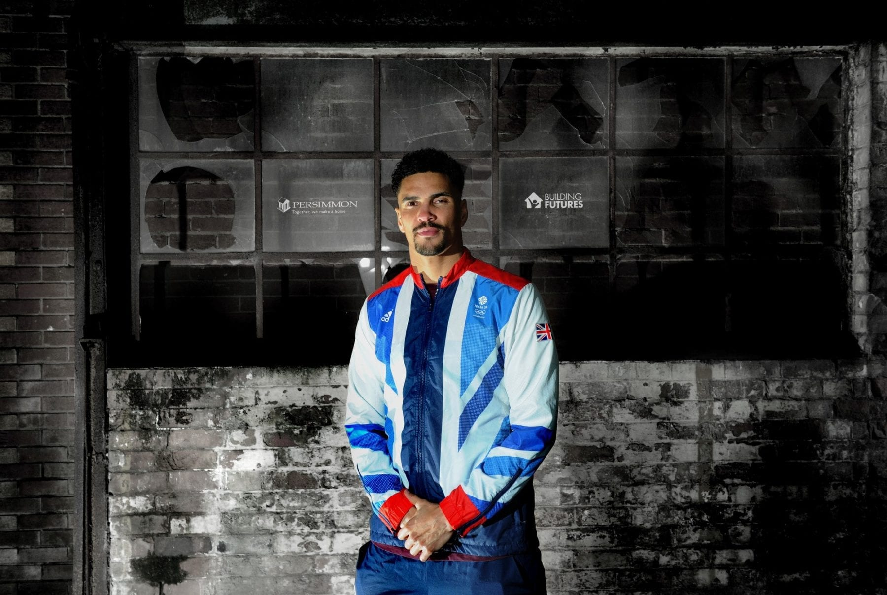 Anthony Ogogo stands against a wall with logos of Persimmon Homes and Building Futures