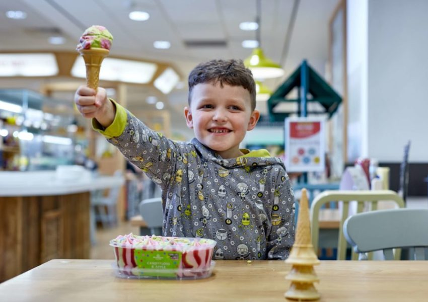 Albie Noble eating candyfloss and apple ice cream, seated at a table, holding up an ice cream cone