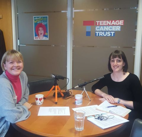 Kate Collins and Beth Crackles seated at a table at Teenage Cancer Trust, recording a podcast