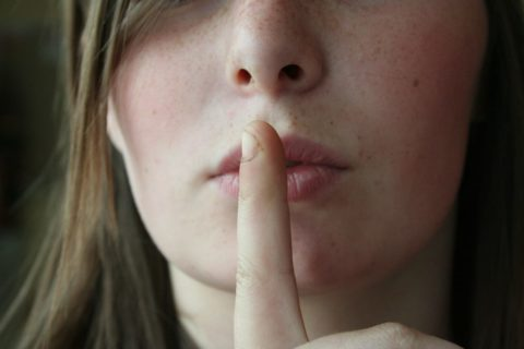 Woman with finger to her lips indicating secrecy - photo: Pixabay