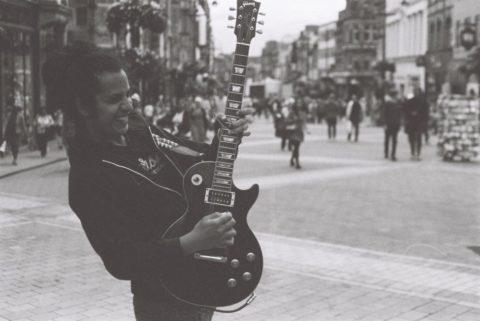 Vito Peleg busking in the street with a guitar. Photo: Tom Sales