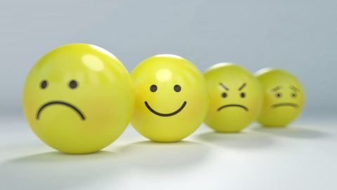 Yellow balls with faces on, like emoji, on a white surface