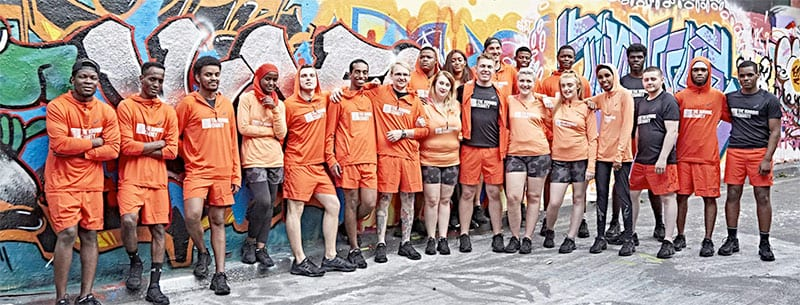 Running Charity runners in orange running gear standing in front of a colourful wall of graffiti