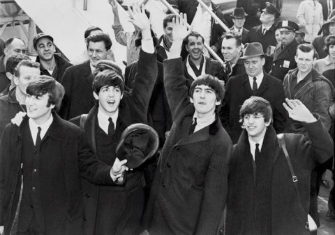 The Beatles wave to fans after arriving at Kennedy Airport.