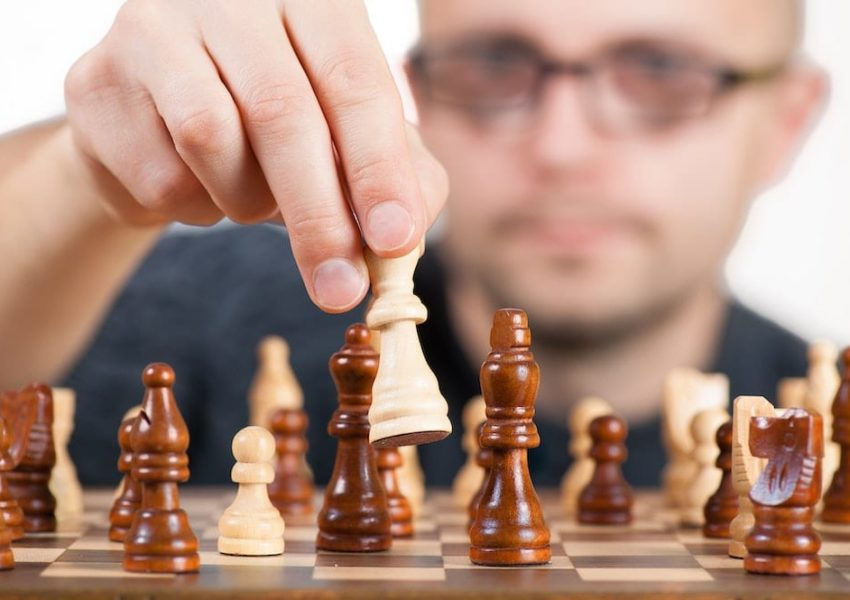Male chess player moving a chess piece