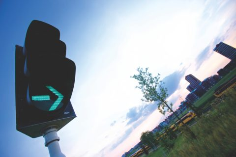 Turn right traffic light against cityscape - photo: Pexels