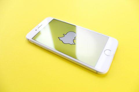Snapchat logo on a phone on a yellow background - photo: Unsplash