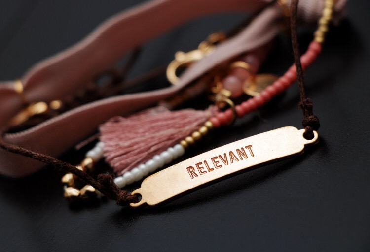 Gold bracelet with 'relevance' engraved on it