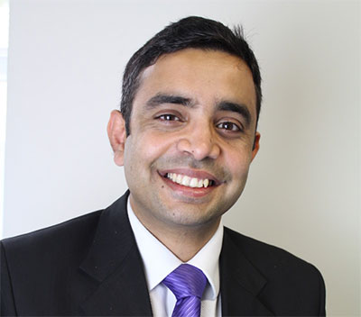Ikhlaq Hussain, smiling and wearing a purple tie