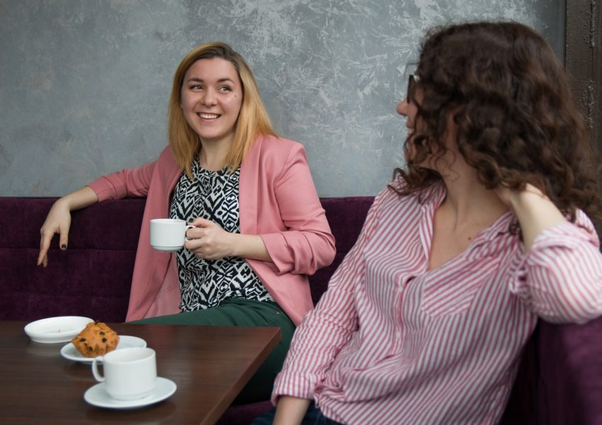 Two women have a conversation in a cafe