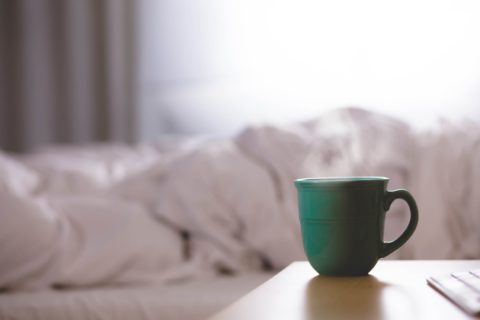 Dormant activity - cup of coffee next to duvet on a bed - photo: Unsplash