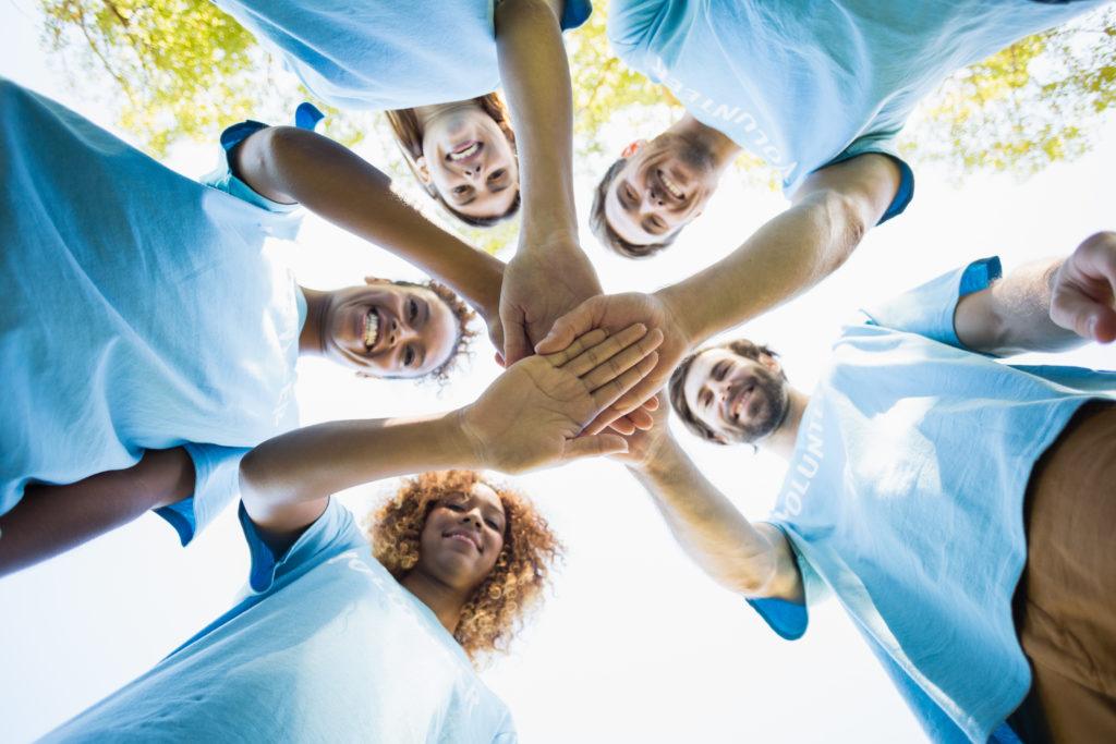 Volunteers hold hands together in star shape