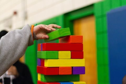 Coloured wooden building block structure, with child's hand. Photo: unsplash.com