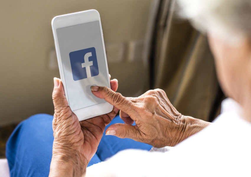 Elderly woman using Facebook application on a phone