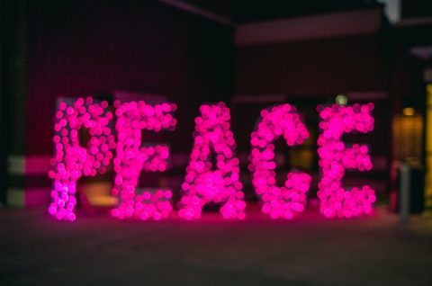 Peace sign in pink letters