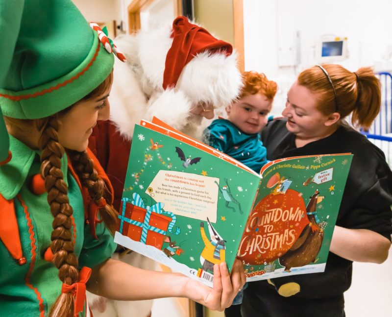 GOSH patient reads a story with GOSH volunteer elves and Father Christmas