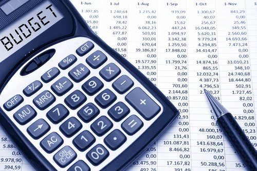 'Budget' in text on a calculator screen, on a spreadsheet print-out with pen