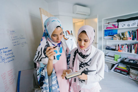 Two women in white hijab veils in an office