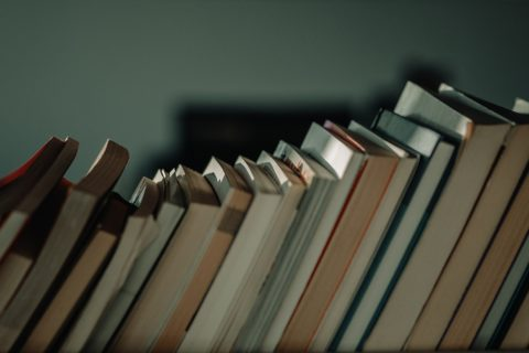 Books on a bookshelf, leaning to the right - Unsplash
