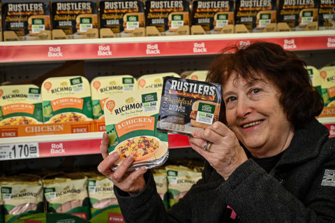 Smiling woman holds Rustlers and Richmond Sausages packets in front of full shelves in Asda