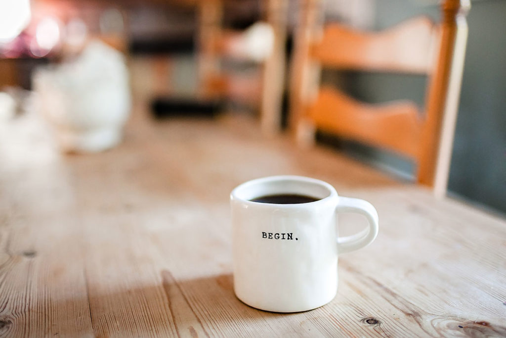 Begin sign on coffee mug on a table - photo: Unsplash
