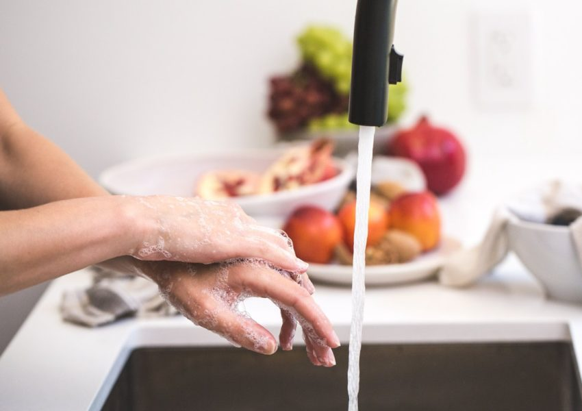 A woman washes her hands under running water in a kitchen