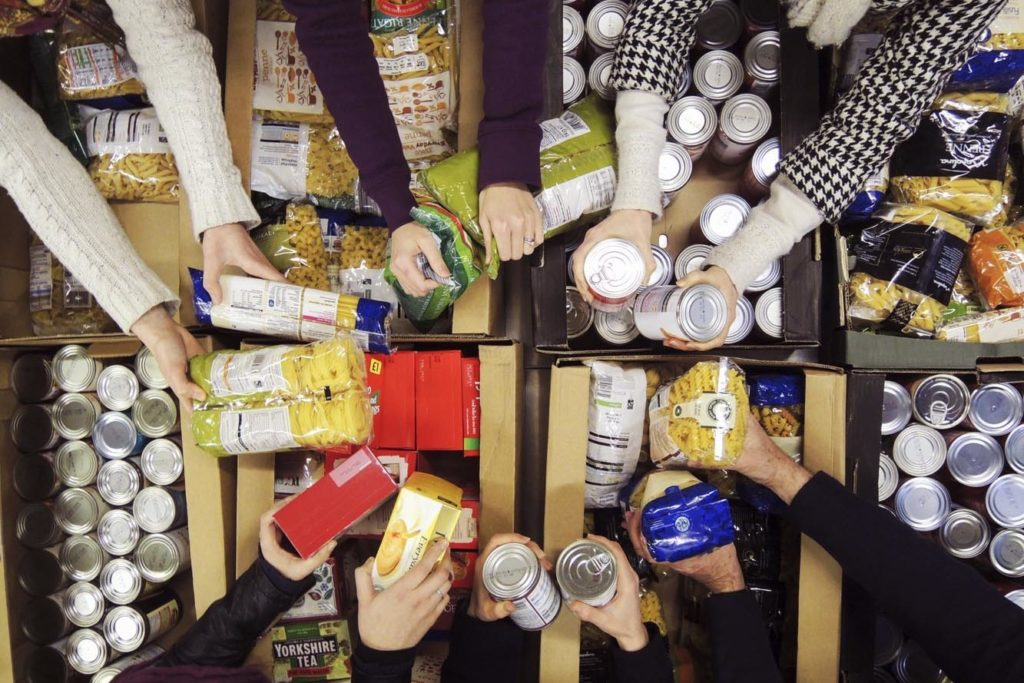 Volunteers sort tins in a foodbank warehouse