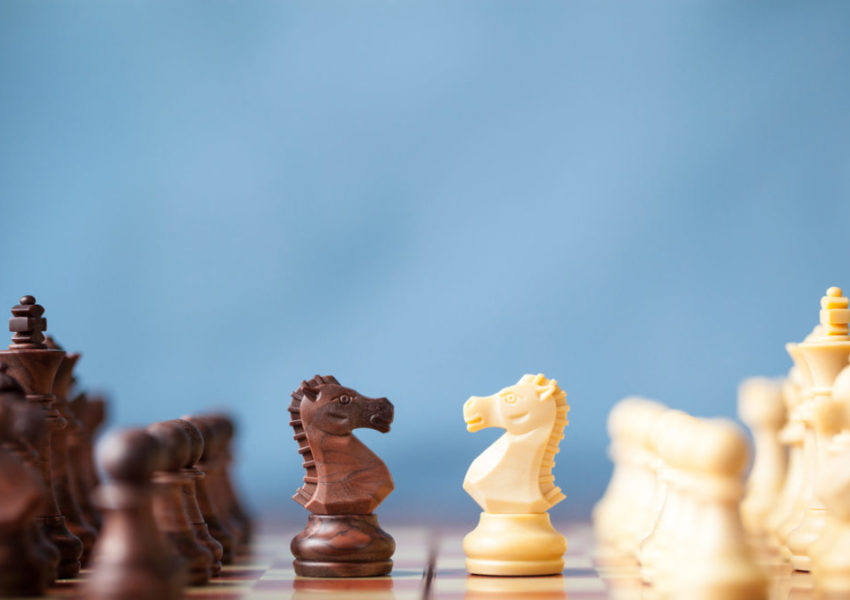 Black and white chess pieces oppose each other