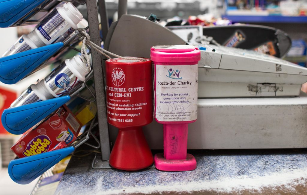 Two charity cash collecting tins on a shop counter